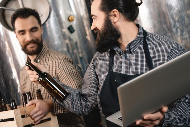 Brewery worker picks up bottles for bottling beer. Production of craft beer. stock photography