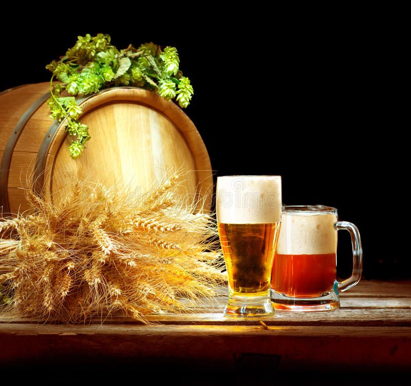 Brewing. Wooden barrel and two mugs with beer royalty free stock photo