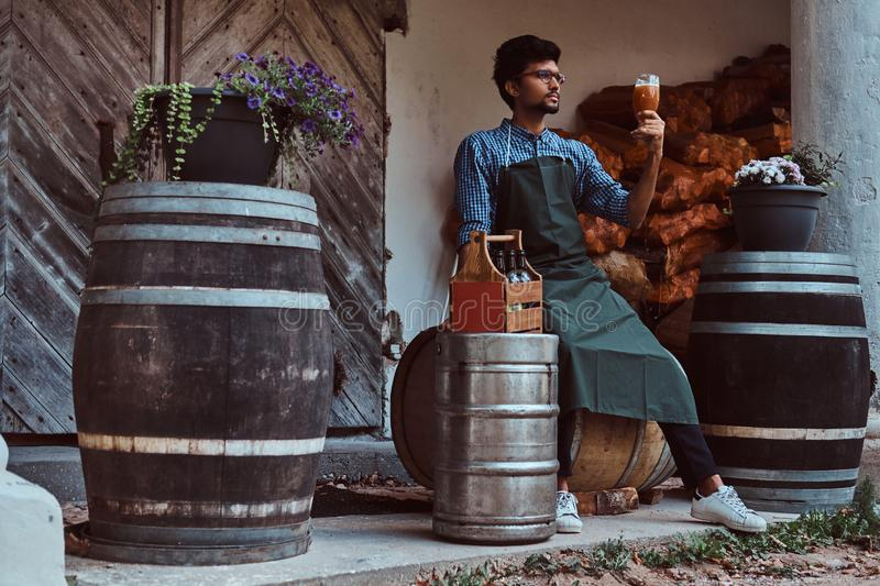 Brewmaster sitting on a wooden barrel and holds a glass of craft beer, relaxes after work. Brewmaster sitting on wooden barrel and holds a glass of craft beer royalty free stock images