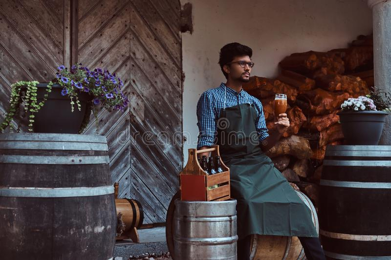 Brewmaster sitting on a wooden barrel and holds a glass of craft beer, relaxes after work. Brewmaster sitting on wooden barrel and holds a glass of craft beer stock images