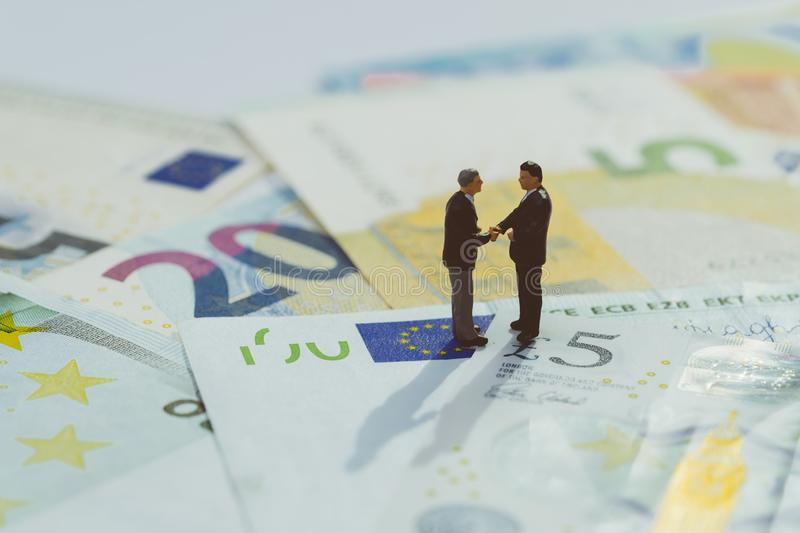 Brexit agreement, Europe and UK economy deal, financial, investment or currency exchange concept, miniature businessman figurine. Hand shaking and looking at stock image