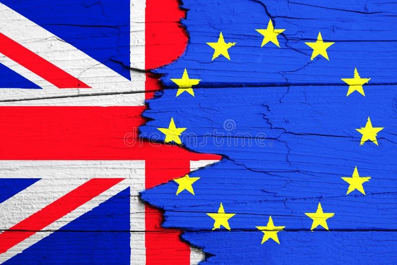 Brexit begrepp: flaggor av EU och Förenadet kungariket UK för europeisk union målade med intensiva ljusa färger på sprucket trä royaltyfri foto