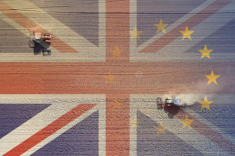 Brexit concept of combine harvesters working on a field over layered with the Union Jack and E.U flag. To represent Brexit royalty free stock photography