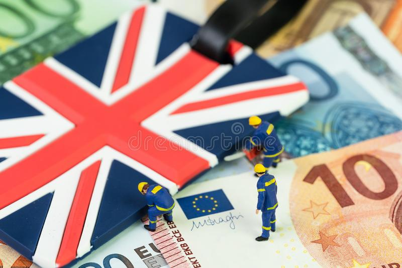 Brexit negotiation plan or Euro zone withdrawal concept, miniature figures worker help move UK Union jack flag from pile of Euro. Banknotes money stock images