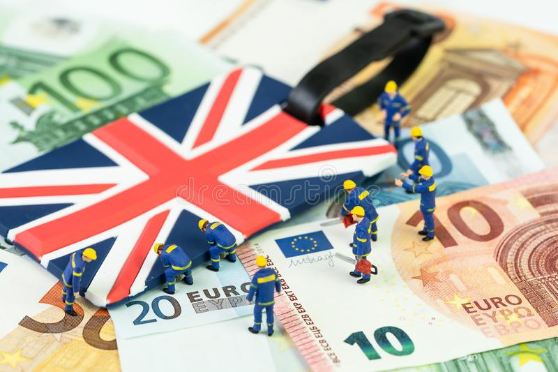 Brexit negotiation plan or Euro zone withdrawal concept, miniature figures worker help move UK Union jack flag from pile of Euro. Banknotes money stock image