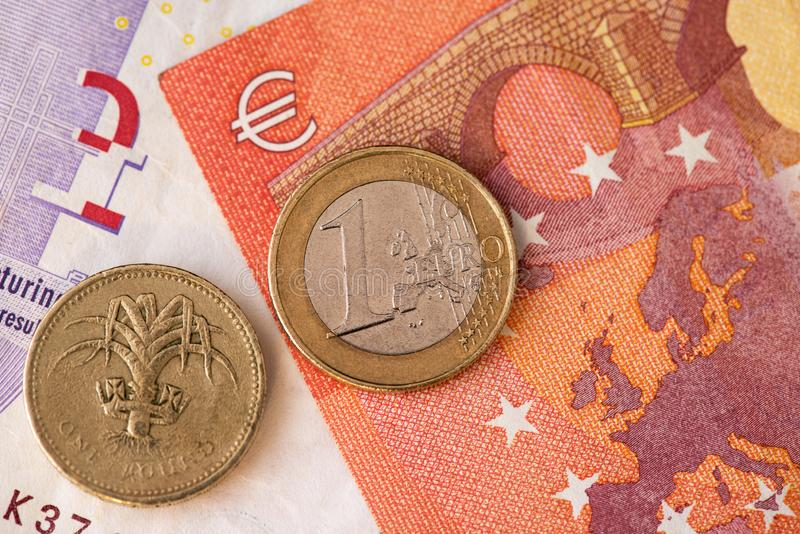 Brexit. One British Pound and Euro coin. GBP EUR. Brexit. Close up view of one British Pound and EURO coin on banknotes. Background Brexit concept GBP EUR Money stock photo