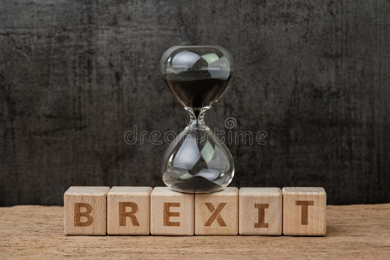 Brexit, time countdown for the UK to deal and withdraw from Euro zone concept, sandglass or hourglass on wooden cube block with. Alphabet building the word stock images