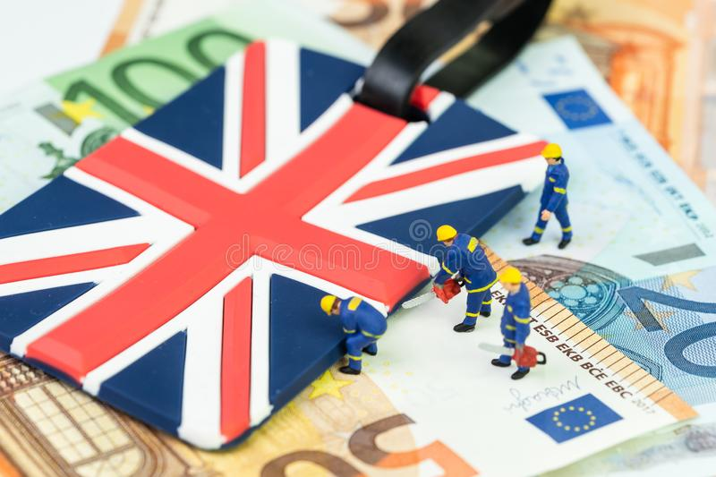Brexit withdrawal plan or Euro zone departure concept, miniature figures worker help cut and move UK Union jack flag from pile of. Euro banknotes money stock images