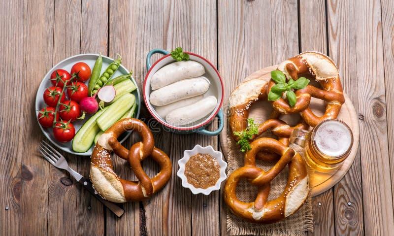 Brezeln, weiße bayerische Würste, Bier und Gemüse auf hölzernem Hintergrund, deutsche traditionelle Nahrung, oktoberfest lizenzfreie stockfotografie