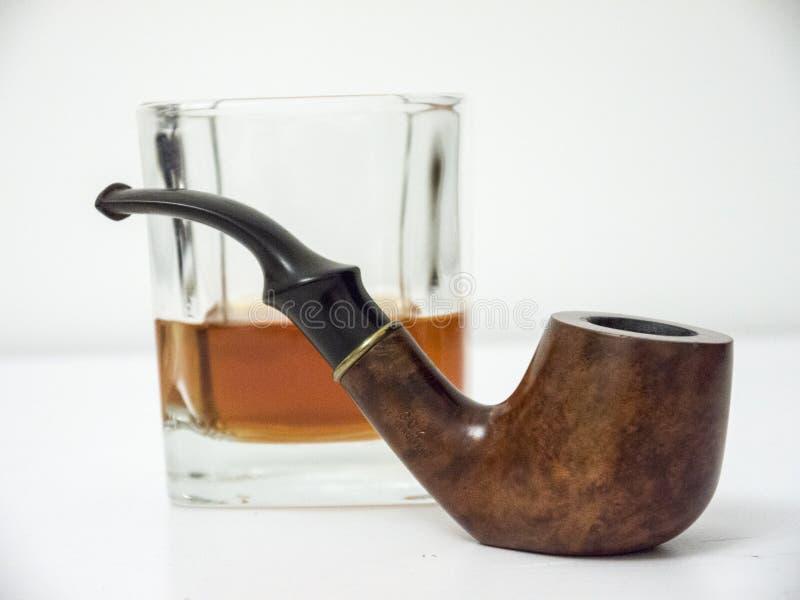 Briar rokende pijp met glas van wisky zijaanzicht met vervormd stock afbeeldingen