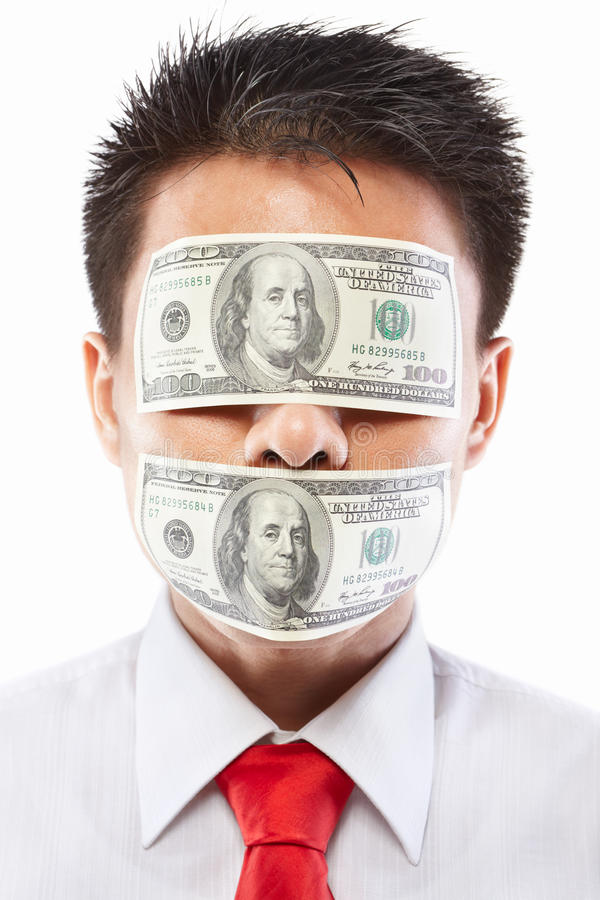 Bribe concept. Chinese young man with his mouth an eyes each sealed by two hundred dollar bills for bribe concept royalty free stock photos