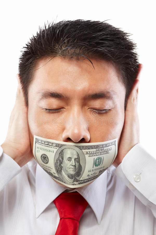 Bribe concept, mouth sealed with dollar bill. Chinese young man with his mouth sealed by a hundred dollar bills for bribe concept stock photos