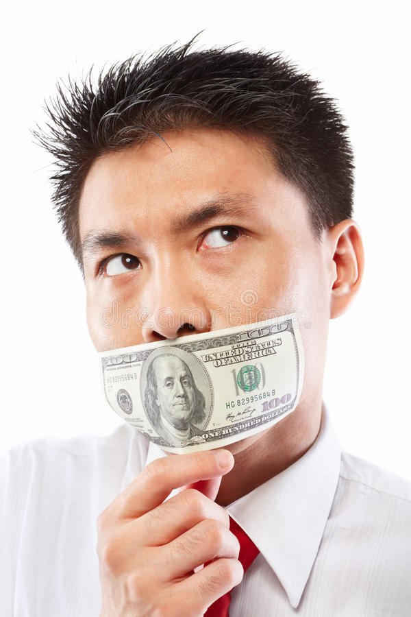 Bribe concept, mouth sealed with dollar bill. Chinese young man with his mouth sealed by a hundred dollar bills for bribe concept royalty free stock images