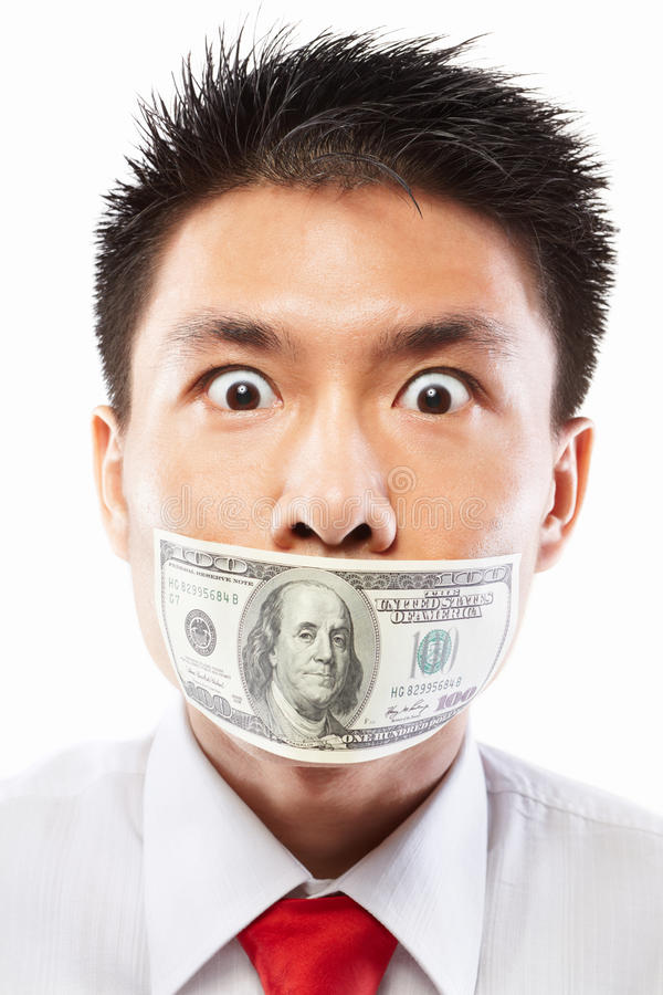 Bribe concept, mouth sealed with dollar bill. Chinese young man with his mouth sealed by a hundred dollar bills for bribe concept stock image