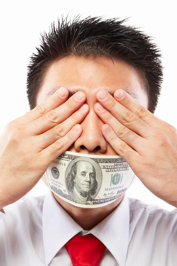 Bribe concept, mouth sealed with dollar bill. Chinese young man with his mouth sealed by a hundred dollar bills for bribe concept royalty free stock photography