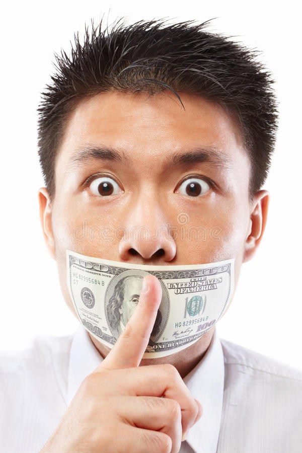 Bribe concept, mouth sealed with dollar bill. Chinese young man with his mouth sealed by a hundred dollar bills for bribe concept stock photo