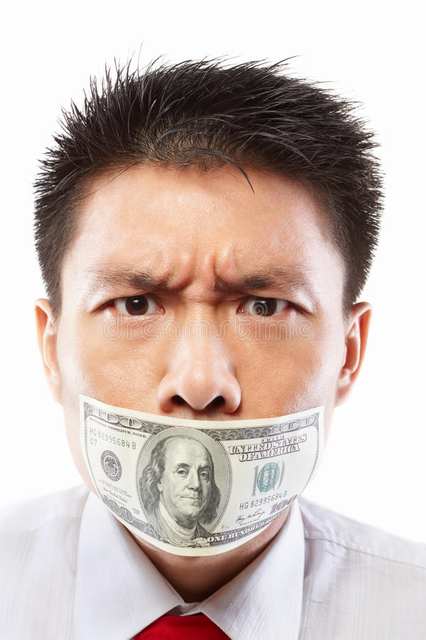 Bribe concept, mouth sealed with dollar bill. Chinese young man with his mouth sealed by a hundred dollar bills for bribe concept royalty free stock photo