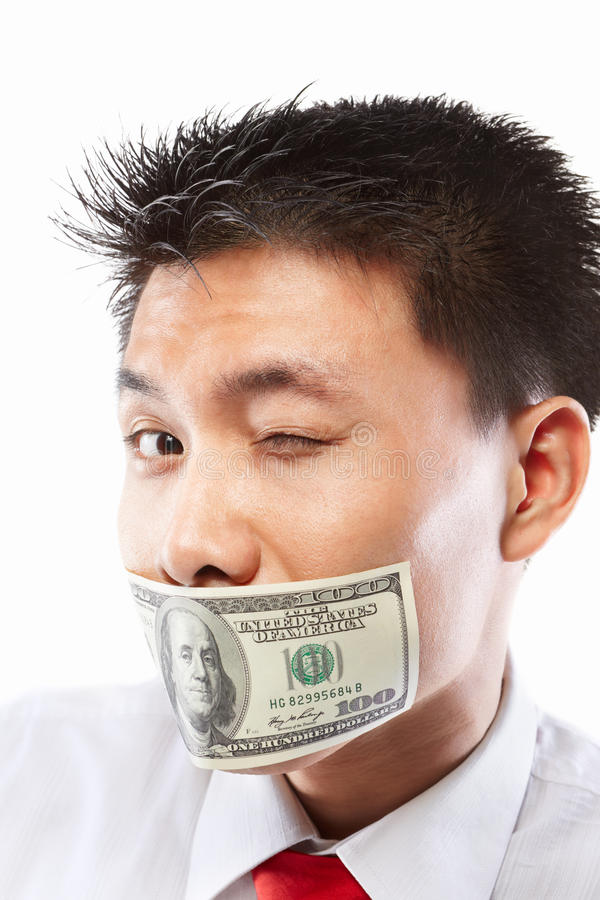Bribe concept, mouth sealed with dollar bill. Chinese young man with his mouth sealed by a hundred dollar bills for bribe concept royalty free stock photos
