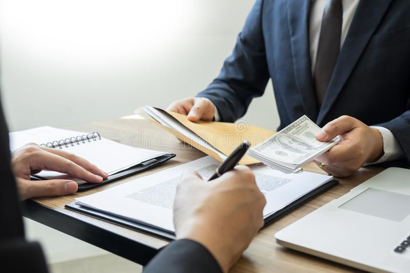 Bribe and corruption concept, Corrupted businessman sealing the deal hand receiving venality bribe money from partner.  royalty free stock image