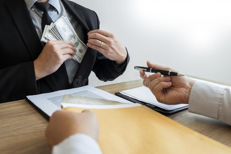 Bribe and corruption concept, Corrupted businessman sealing the deal hand receiving venality bribe money from partner.  stock photo