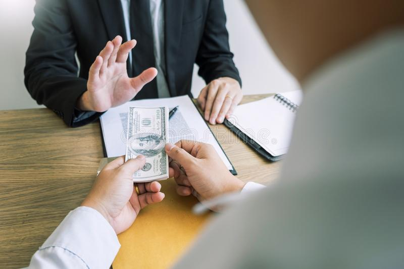 Bribe and corruption concept, Corrupted businessman sealing the deal hand receiving venality bribe money from partner.  stock photos