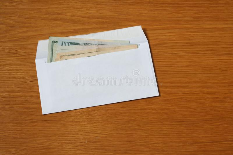 Some US dollars banknotes in the white black envelope for a bribe in the office on the table. Bribe of some US dollars banknotes in the blank white envelope over royalty free stock images