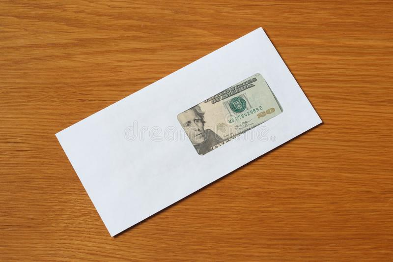 Some US dollars banknotes in the white black envelope for a bribe in the office at the table. Bribe of some US dollars banknotes in the blank white envelope over stock photo