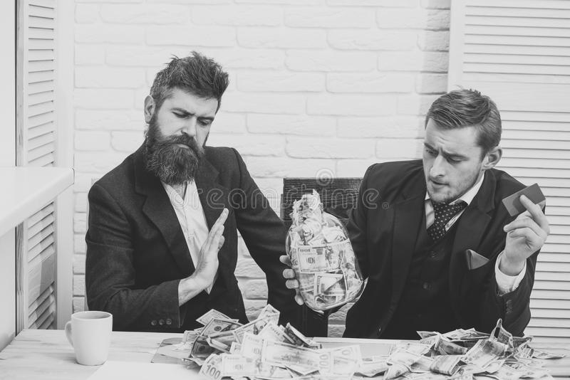 Bribe taker. Business partners, businessmen at meeting in office. Bearded boss refuses of lot of cash, colleague holds. Credit card. Cash and banking concept stock photography