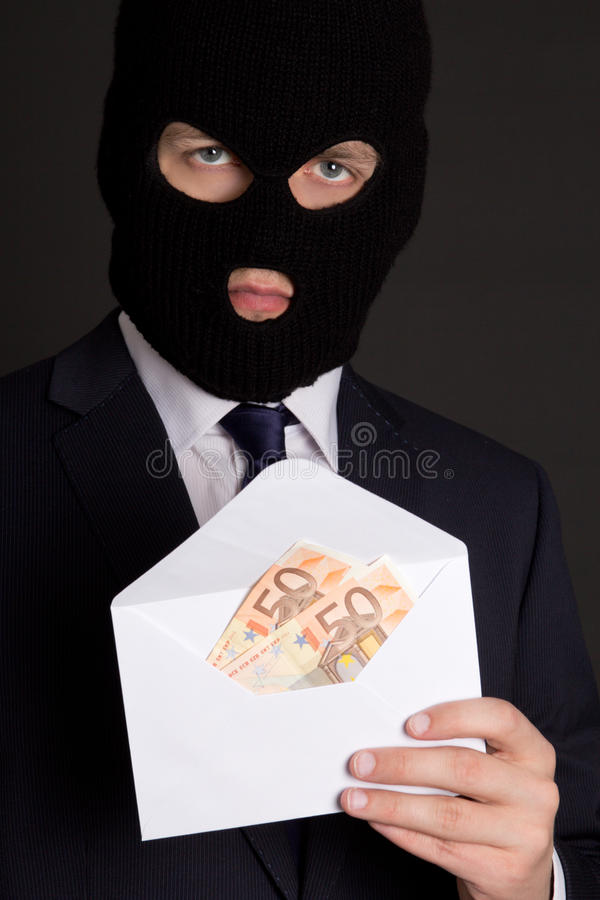 Bribery concept - masked man in suit holding envelope with euro. Bribery concept - masked man in business suit holding envelope with euro banknotes stock photo