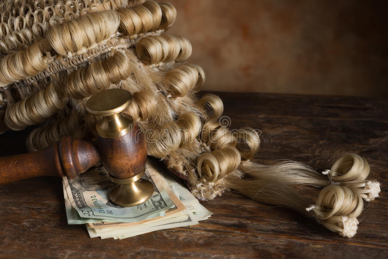 Bribery and corruption in court. Bribery or corruption in court symbolized with money and a judge's wig royalty free stock image