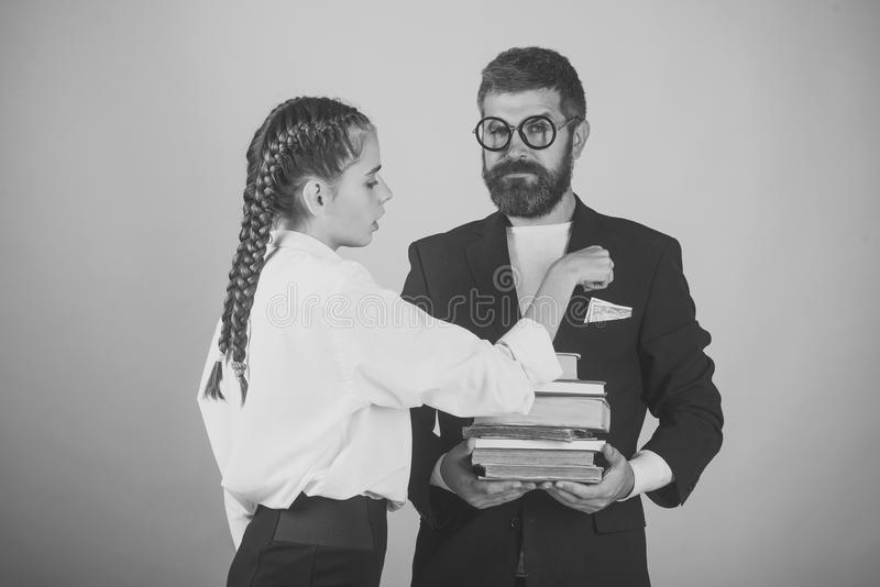 Bribes for study. Father and schoolgirl with serious faces on yellow background. Teenager takes pocket money and dad holds pile of books. Education and back to royalty free stock image