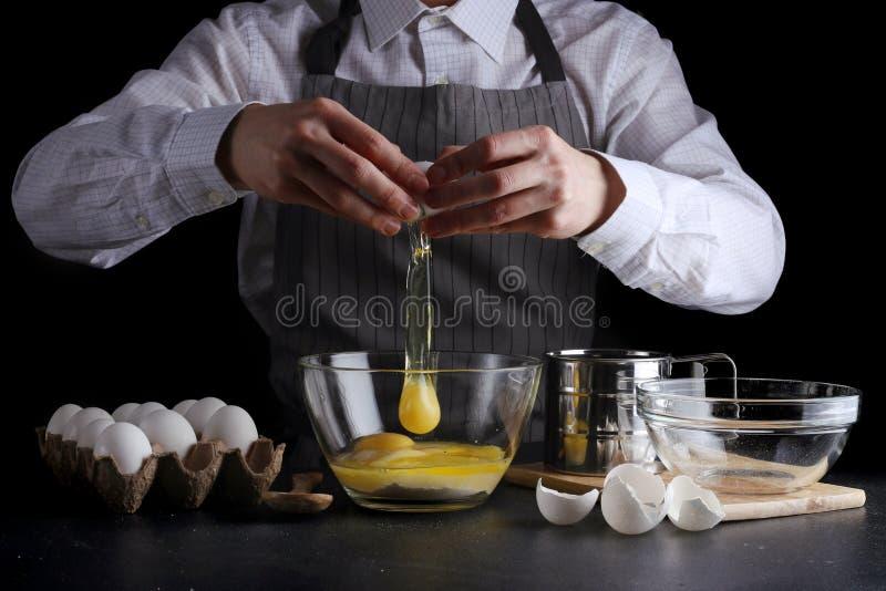 Bricht das Ei f?r Teig Rezepttorte oder -kuchen, die Konzept auf dunklem Hintergrund machen stockbild
