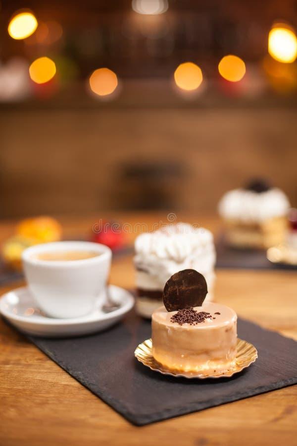 Briciole di chocholate su un dessert saporito con il biscotto sulla cima sopra una tavola di legno vicino ad un caffè delizioso immagini stock