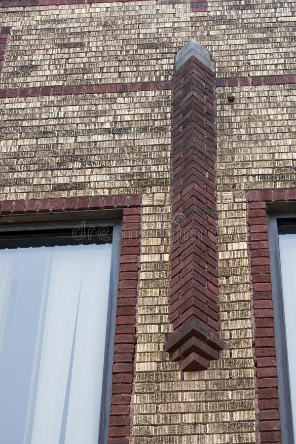 Brick accent on building. A design accent of red brick on an old building of lighter yellow brick stock photography