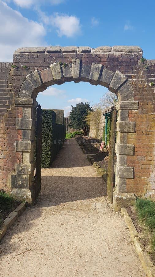Brick arch gateway in formal garden. stock photography