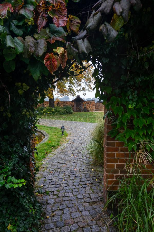 Brick arch twined with plants. Village courtyard stock photo