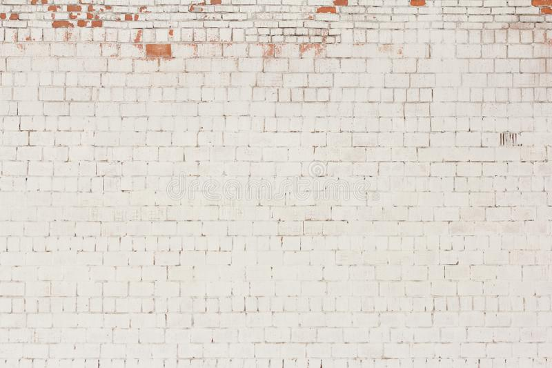 Brick background, old brick wall painted white and with fallen off plaster royalty free stock image