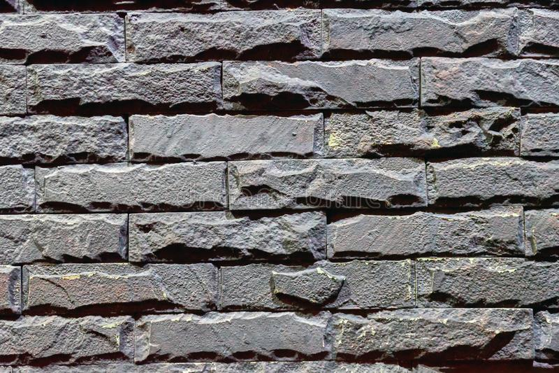 Brick background, wall backdrop with rough texture, grey stonework with uneven rectangular shape. Grungy material. royalty free stock image