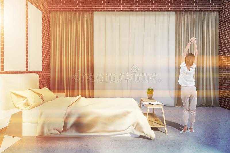 Brick bedroom with poster gallery, woman stock images
