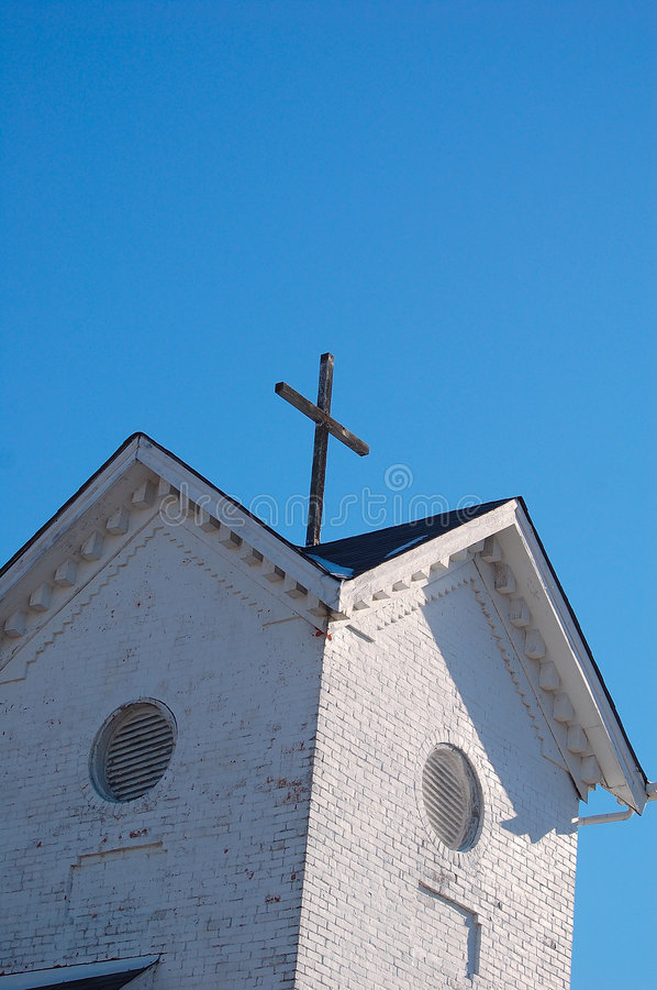 Brick built church tower with cross. Whitewashed brick built church bell tower with Christian cross on top with a cloudless blue sky background stock image
