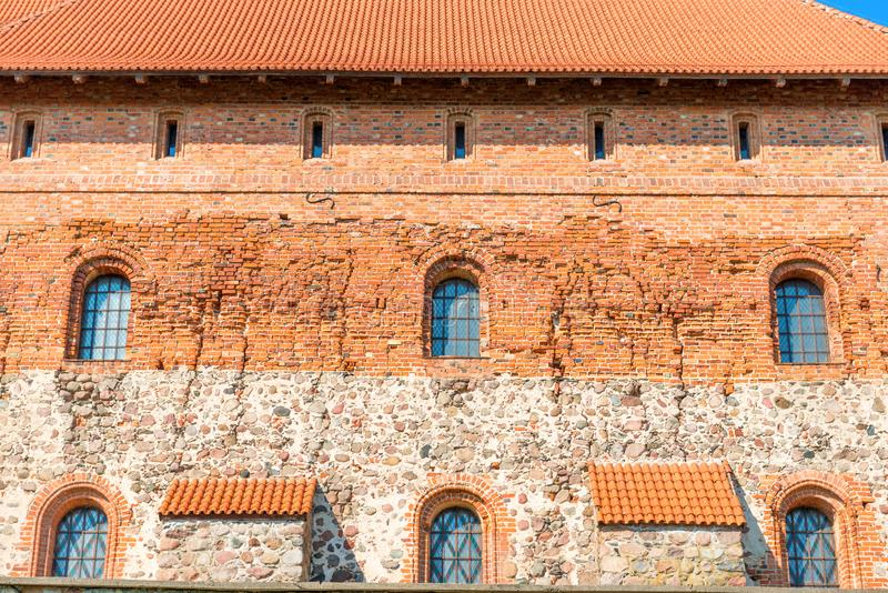 Brick castle wall with windows. Old brick castle wall with windows and tile roof royalty free stock photography
