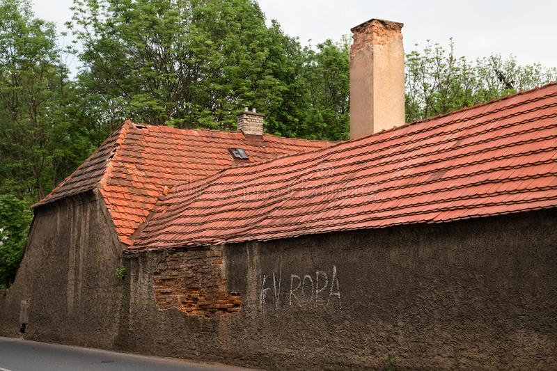 Brick chimney red roof old building with damaged brick wall. stock photography