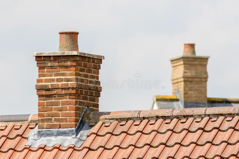 Brick chimney stack on modern contemporary house roof top stock photography