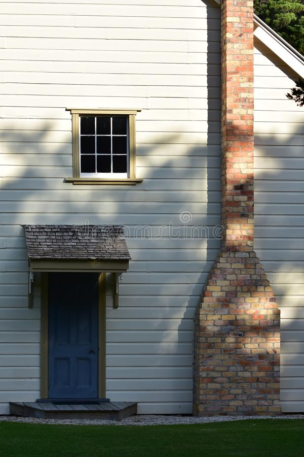 Brick chimney of wooden villa. Side wall of vintage wooden hotel with small door and tall brick chimney in Mahurangi Harbour near Auckland stock photo