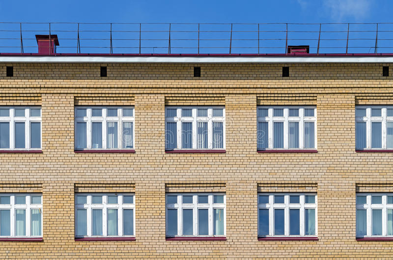 Brick facade of the house with a roof and white windows against the blue sky. Texture, background series stock photos