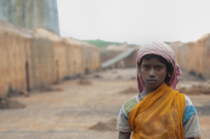 Brick Factory in India. KOLKATA - OCTOBER 26 : A teenage girl - one of many girls working in brick manufacturing industry where they live and work under royalty free stock photography
