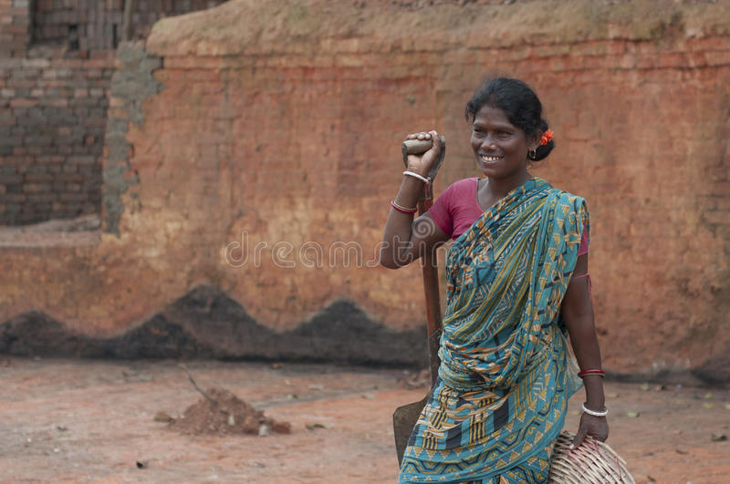 Brick Factory in India. KOLKATA - OCTOBER 26 : A woman worker smiling -one of many women working in brick manufacturing industry where they live and work under royalty free stock photography
