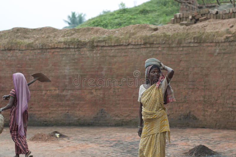 Brick Factory. KOLKATA - OCTOBER 26 : Women workers working in brick manufacturing industry where they live and work under unhealthy and unsafe conditions on stock photography
