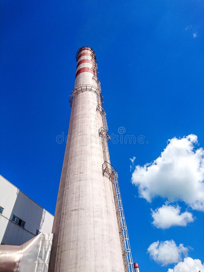 Brick factory pipe on a background of blue sky with white clouds. Bottom view. The concept of cleaner production stock photography