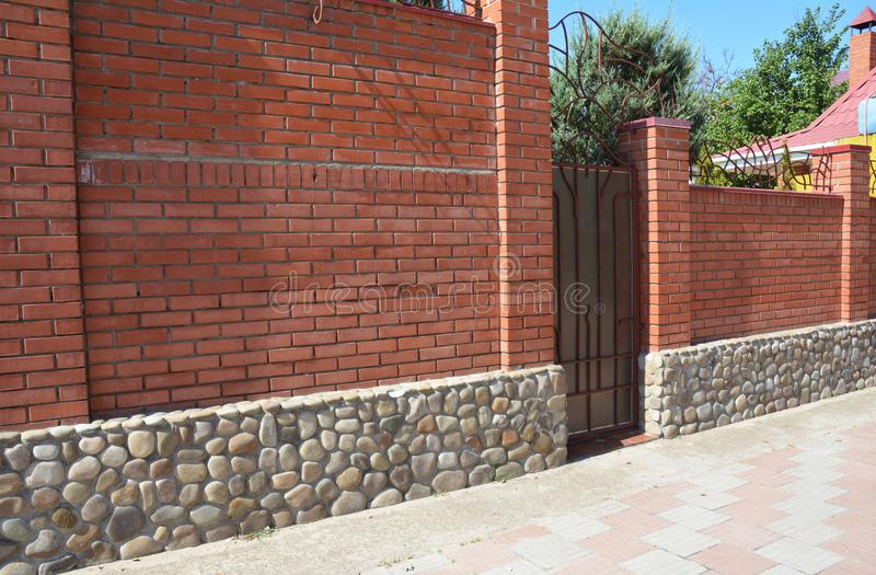 Brick fence with cozy fence sea stone foundation and frame metal door stock images